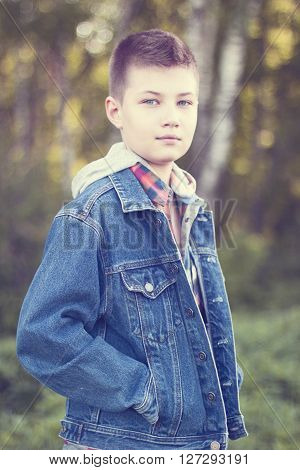 A young boy stands in a park on a meadow on a sunny day, jeans jacket, shirt looks into the distance, the concept of children's fashion style outfit one on vacation