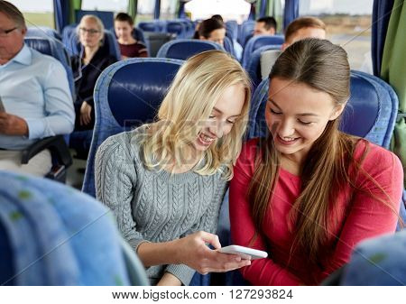 transport, tourism, road trip and people concept - happy young women or friends in travel bus texting or reading message on smartphone