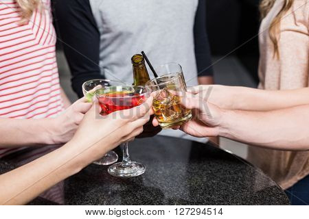 Group of friends toasting with beer and cocktails in a nightclub