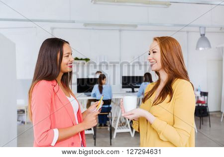business, startup and people concept - happy creative women talking at office