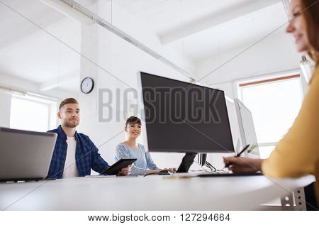 business, startup, technology and people concept - happy creative team with computers at office