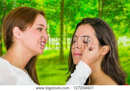 Woman performing eyebrow hair removal using tweezers on clients face, uncomfortable facial expressions, green garden background.