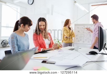 business, startup, planning, strategy and people concept - happy creative team with tablet pc computer and flip board on conference at office