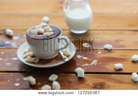 unhealthy eating, object and drinks concept - close up of lump sugar heap drowned in cup of coffee on wooden table