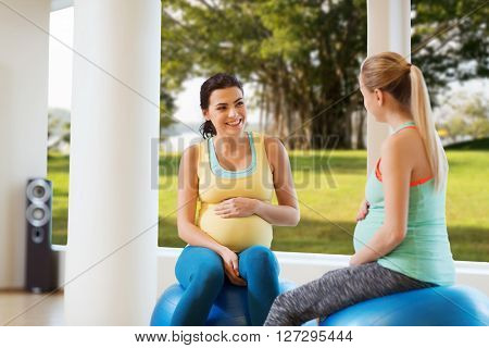 pregnancy, sport, fitness, people and healthy lifestyle concept - two happy pregnant women sitting and talking on balls in gym over natural window view background