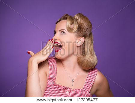 Happy surprising pin-up girl looking away and closing her mouth. Blond lady with red lips posing for photographer isolated on violet background.