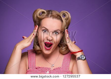 Surprised and astonisherd pin-up girl touching her head. Sexy lady with blond hair happy smiling for photographer isolated on violet.