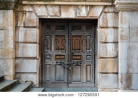 Ancient double wooden doors with lock and chain