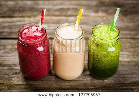 Three milkshakes and smoothies on wooden table