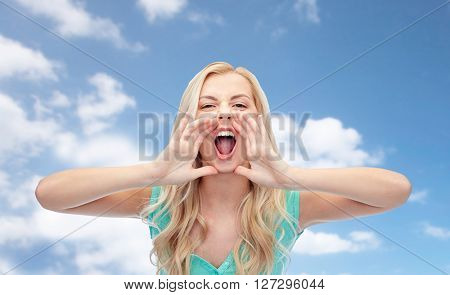 emotions, expressions and people concept - angry young woman or teenage girl shouting over blue sky and clouds background