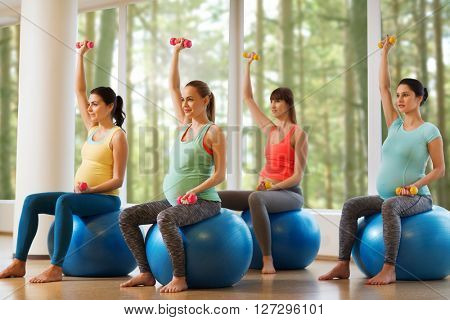 pregnancy, sport, fitness, people and healthy lifestyle concept - group of happy pregnant women with dumbbells exercising on ball in gym