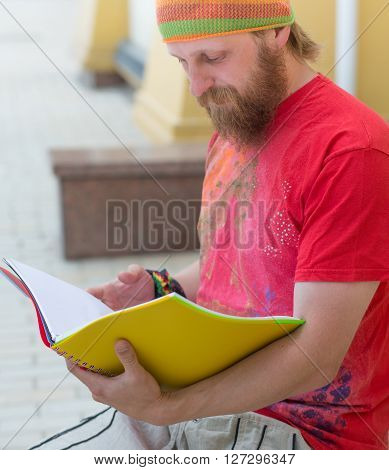 Portrait of happy hipster bearded freelancer man reading his notebook outdoors. Man in red T-shirt working in the city centre in lunch time.