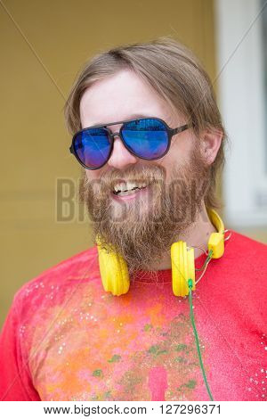 Smiling hipster bearded freelancer man concept. Blond man smiling and wearing sunglasses. Man with earphones showing his white teeth.