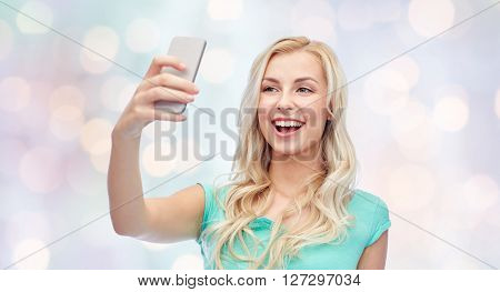 emotions, expressions and people concept - happy smiling young woman or teenage girl taking selfie with smartphone over holidays lights background