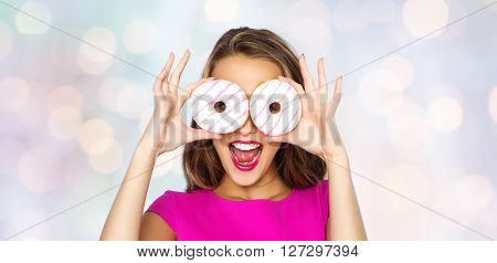 people, holidays, junk food and fast food concept - happy young woman or teen girl in pink dress having fun and looking through donuts over holidays lights background