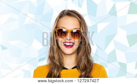 people, style and fashion concept - happy young woman or teen girl face in sunglasses over low poly blue background