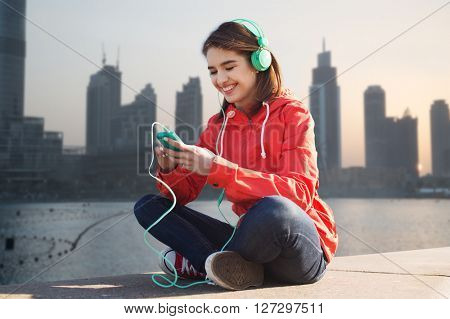 technology, lifestyle and people concept - smiling young woman or teenage girl with smartphone and headphones listening to music over dubai city street background