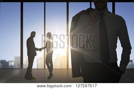 business, teamwork, partnership, cooperation and people concept - business people shaking hands over office background