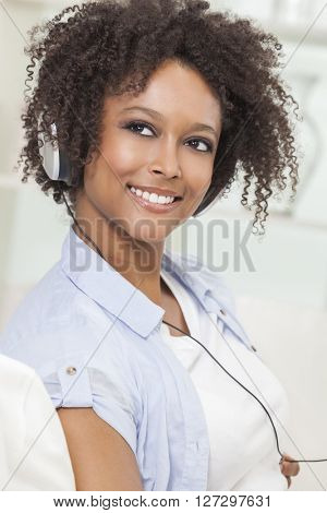 A beautiful mixed race African American girl or young woman listening to music on mp3 player and headphones