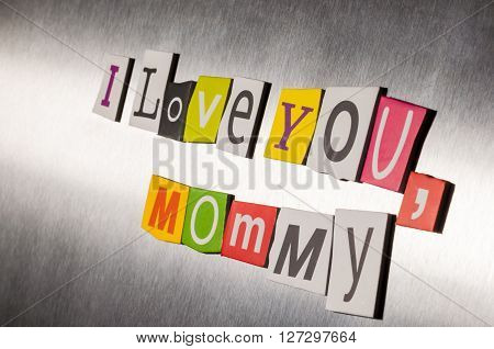 Mothers day message of color magazine letter clippings on metal background. I love you mom or mommy. Selective focus.