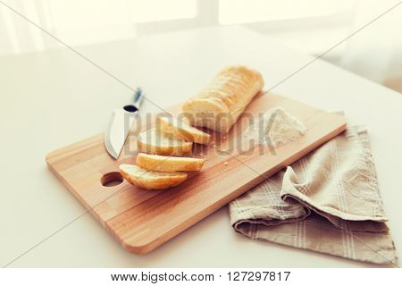 food, junk-food, diet and unhealthy eating concept - close up of white bread or baguette and kitchen knife on wooden cutting board