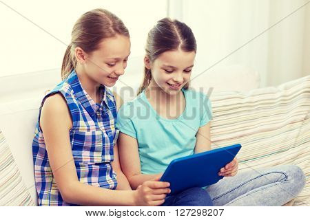 people, children, technology, friends and friendship concept - happy little girls with tablet pc computer sitting on sofa at home
