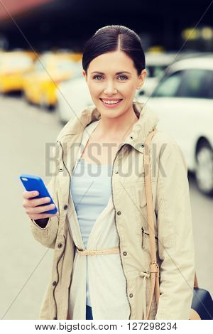 travel, business trip, people and tourism concept - smiling young woman with smartphone over taxi station or city street