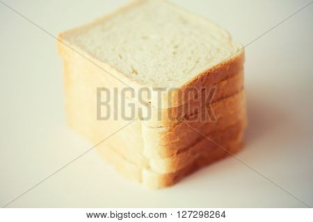 food, junk-food and unhealthy eating concept - close up of white toast bread on table