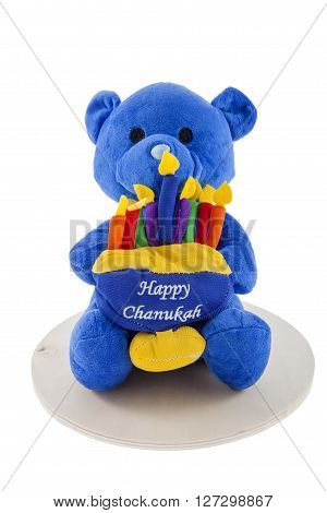 A toy bear holding a menorah against a white background