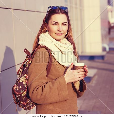 Beautiful brunette woman holding a bag and a cup of hot tea or coffee, standing in the street in a beige coat with glasses resting, eating breakfast in the spring or autumn