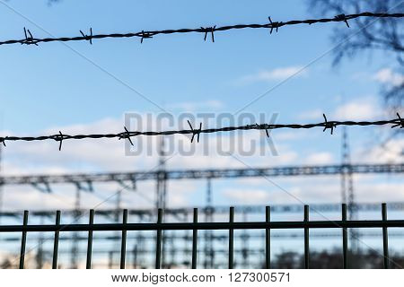 Electricity pylon and barrier fence against  blue sky
