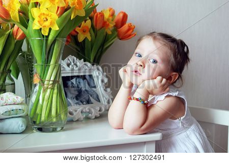 Beautiful small kid girl with flowers in studio