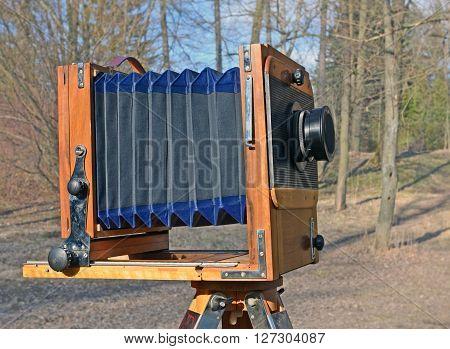 The old vintage large-format camera against blur of spring park.