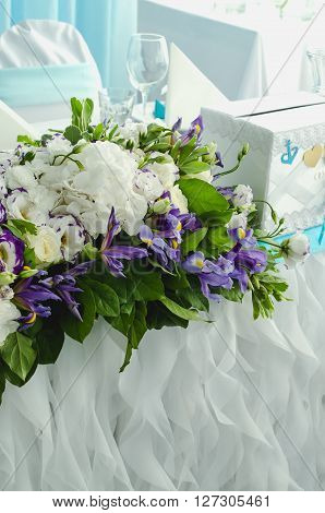 Luxury table beautiful rich decoration with lush leaves white hydrangea delicate cream roses purple eustoma blue iris in restaurant. Style summer sea wedding concept. Floral arrangement design.