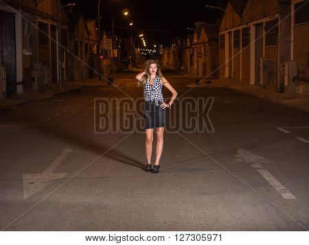 pretty blonde standing on the road at night with one hand on the hair