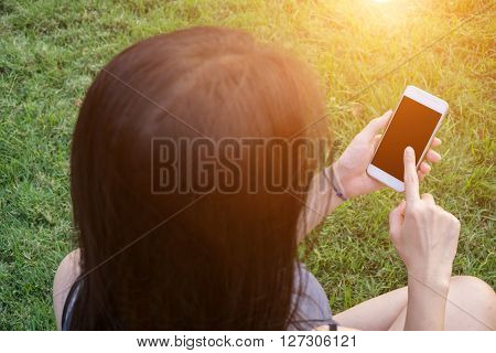 Young Woman Touching Smartphone On Green Grass