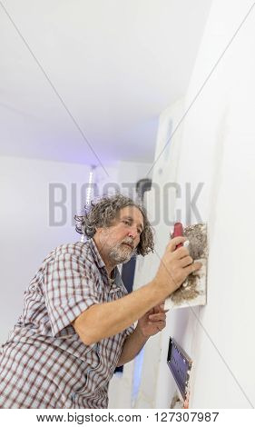 Middle-aged man worker builder or homeowner plastering a white wall preparing it for painting as he repairs a crack or some other imperfection.