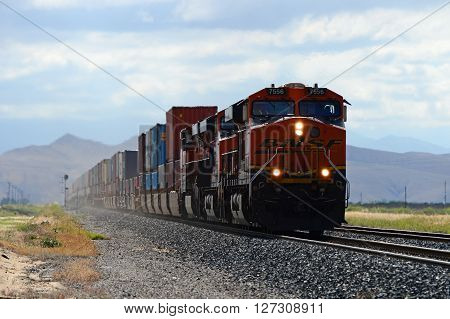 KERN COUNTY, CA - APRIL 23, 2016: A BNSF freight train speeds out of the Sierra Nevada Range into the southern San Joaquin Valley, westbound through Tehachapi to Bakersfield.