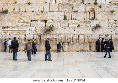 JERUSALEM ISRAEL - MARCH 15 2016: People at the men's section of the Wailing (Western) Wall in the old town Jerusalem (Israel)