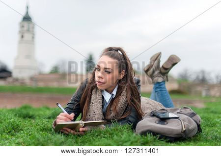 Beautiful girl writing in a book. Girl student in park writes in writing book