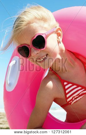 Happy little girl in swimsuit playing with a lifebuoy on the seaside.