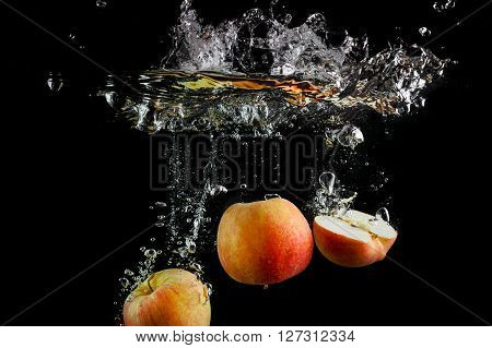 Apples falling into the water with a splash and air bubbles. Fresh apples in water on black background. Healthy food. Wash fruits.