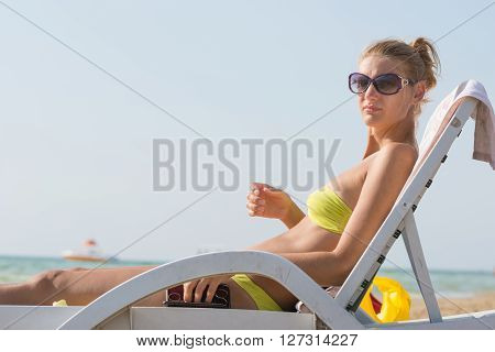Girl On A Deck Chair On The Beach Is Going To Do A Manicure