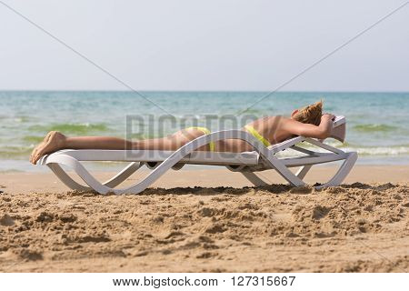 Young Slim Tanned Woman On Sea Beach Lying On Deckchair Face Down