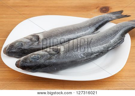 The raw seabass fish on the plate