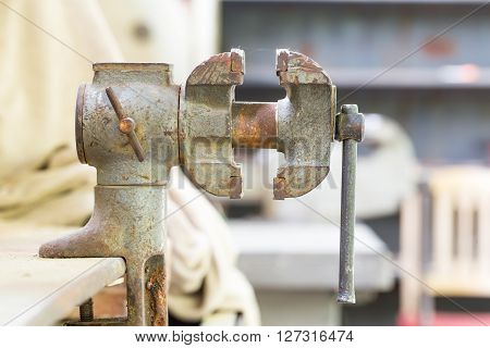 Old bench metal vise in the workshop.