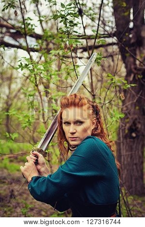 Redhead serious scandinavian woman posing with sword in a wood