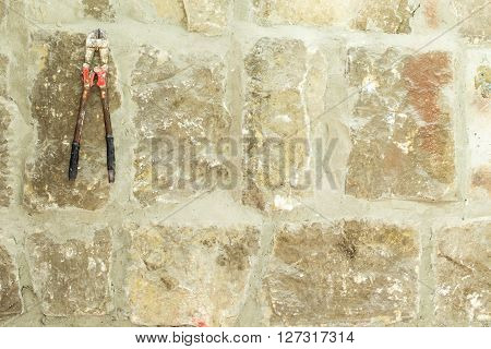 Old moldy stone wall with work scissors. Photo can be used as a whole background.