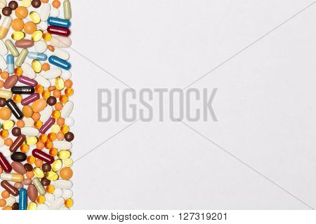 Blank page with border of multi-colored pills and capsules. Concept for the pharmaceutical and medical design