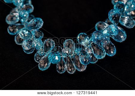 Blue topaz necklace fragment isolated on black background